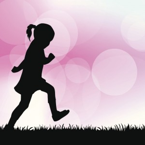 Silhouette of child walking on grass