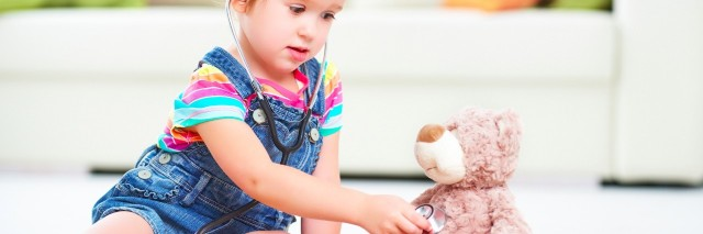 Child holding stethoscope to teddy bear's chest in home living room