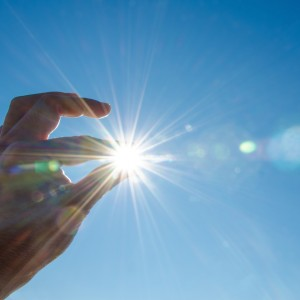A hand stretched out, so it looks like it's holding the sun