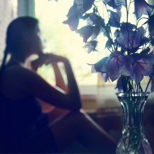 woman staring out of a window next to a vase of purple flowers
