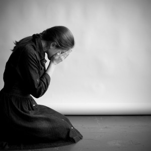 grieving woman on her knees with her face in her hands