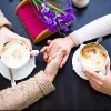 two people drinking coffee and holding hands