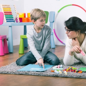 Child and teacher or therapist drawing with chalk on floor