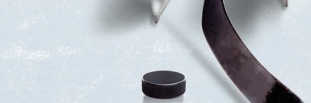 Close-up of hockey player's skates on ice with hockey stick in front of hockey puck
