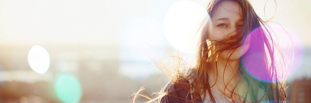 Woman looking at camera, standing in sunset light with wind blowing hair in front of face