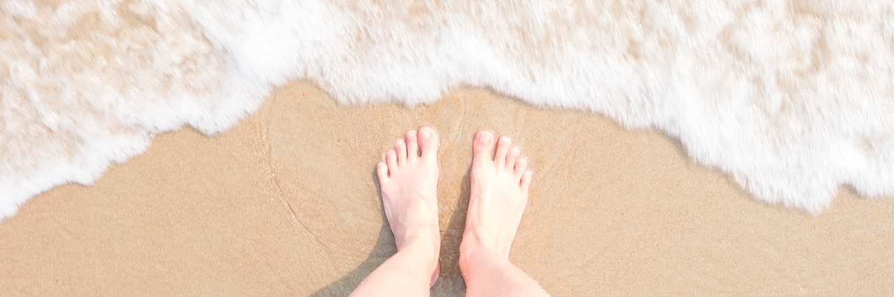 bare feet standing on the beach by the water