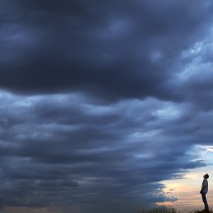 man standing in a field and facing a storm