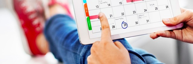 woman sitting on couch with feet up looking at calendar on tablet