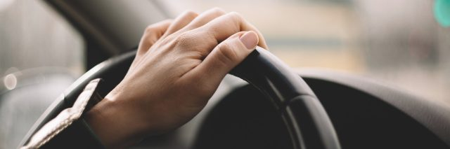 close up of woman's hand driving car