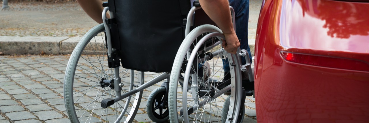 Man in a wheelchair near car.