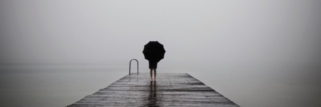 Woman with a umbrella on a dock