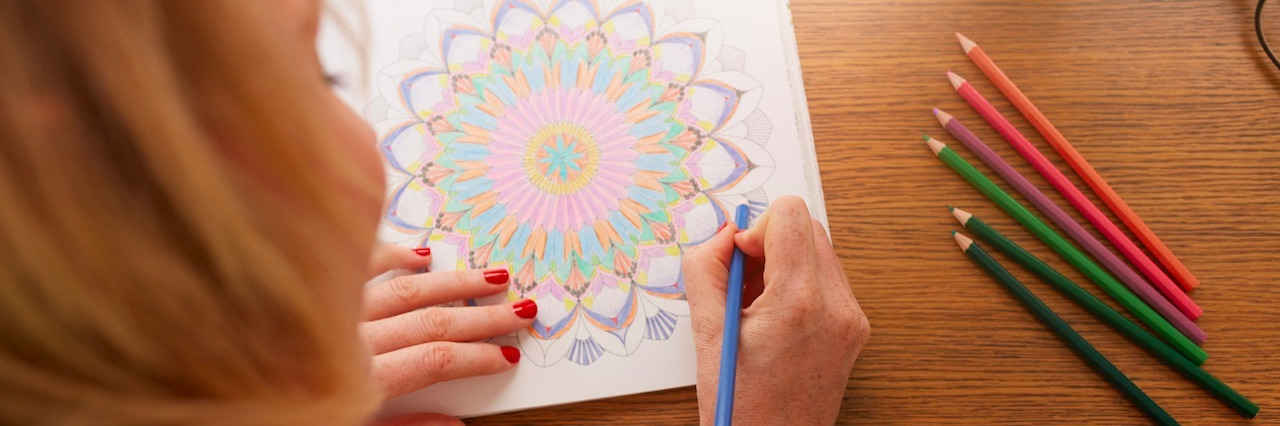 Overhead view of woman drawing in adult coloring book with color pencils.
