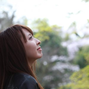 Profile of woman with gaze directed up, with trees in the background