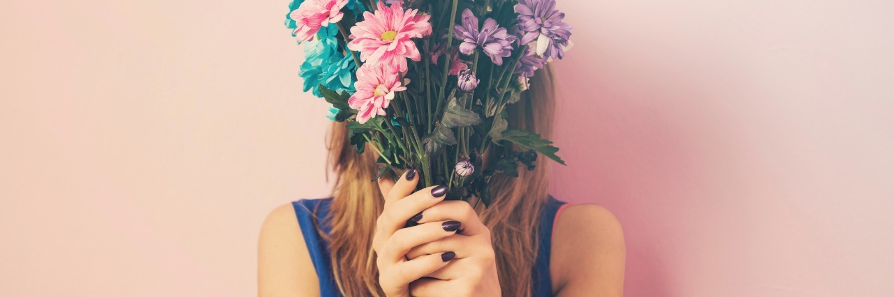 woman holding a bouquet of colorful flowers in front of her face
