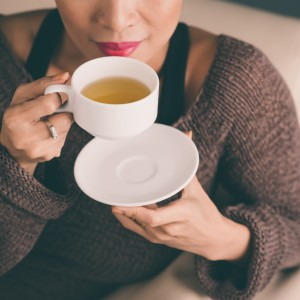 woman holding a hot cup of tea and blowing on it