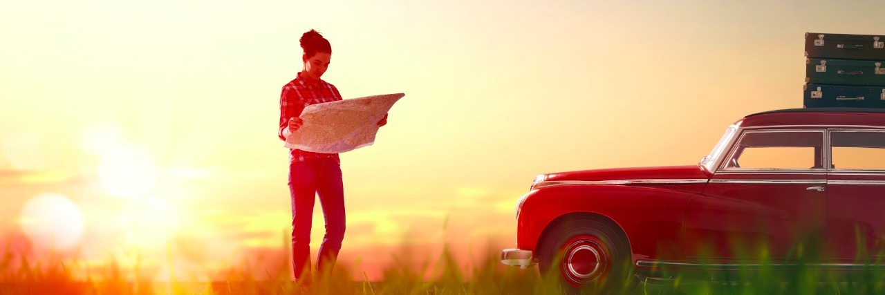 woman standing next to car holding a map