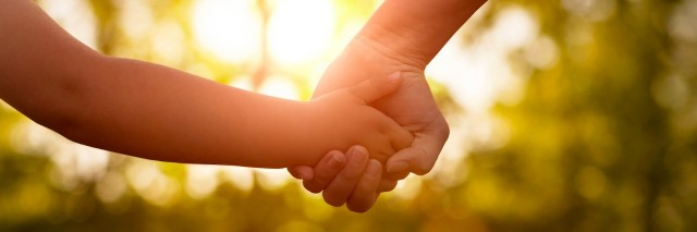 Parent and child holding hands outdoors with trees and sunlight in the background