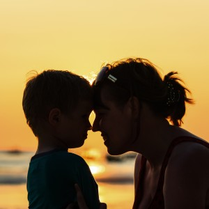 happy loving mother and little son at sunset beach
