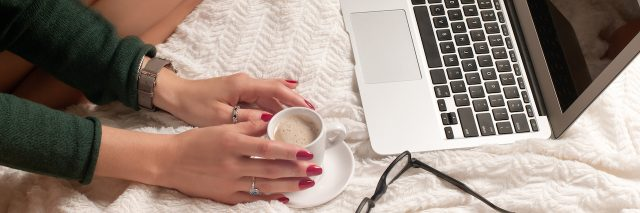 A woman holding a cup of tea sitting on front of her laptop