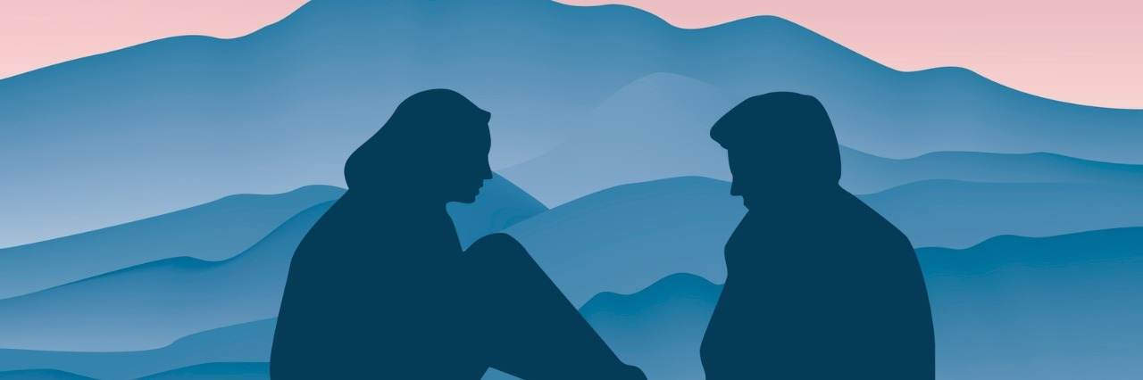 Couple face to face, side view, silhouette in front of a mountain at sunset.