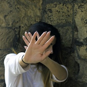 woman standing in front of a stone wall and holding her hands up to block her face