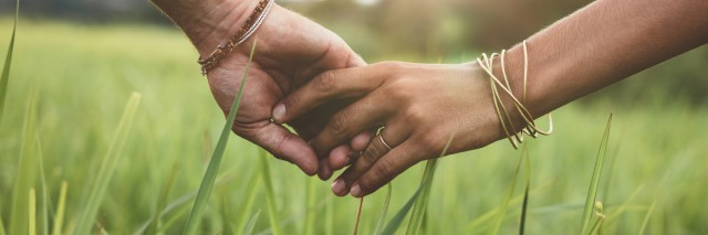 Romantic couple holding hands in a field.