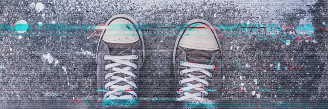 Pair of sneakers on pavement with digital glitch effect, young adult man standing on concrete flooring