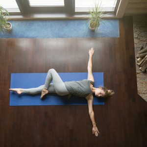 young woman working out in living room, doing yoga exercise on wooden floor