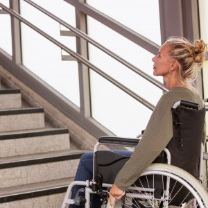 Woman in a wheelchair in front of stairs.