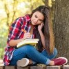 college student sitting on a bench outside next to a tree with books and a journal