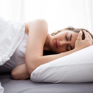 woman on bed having headache