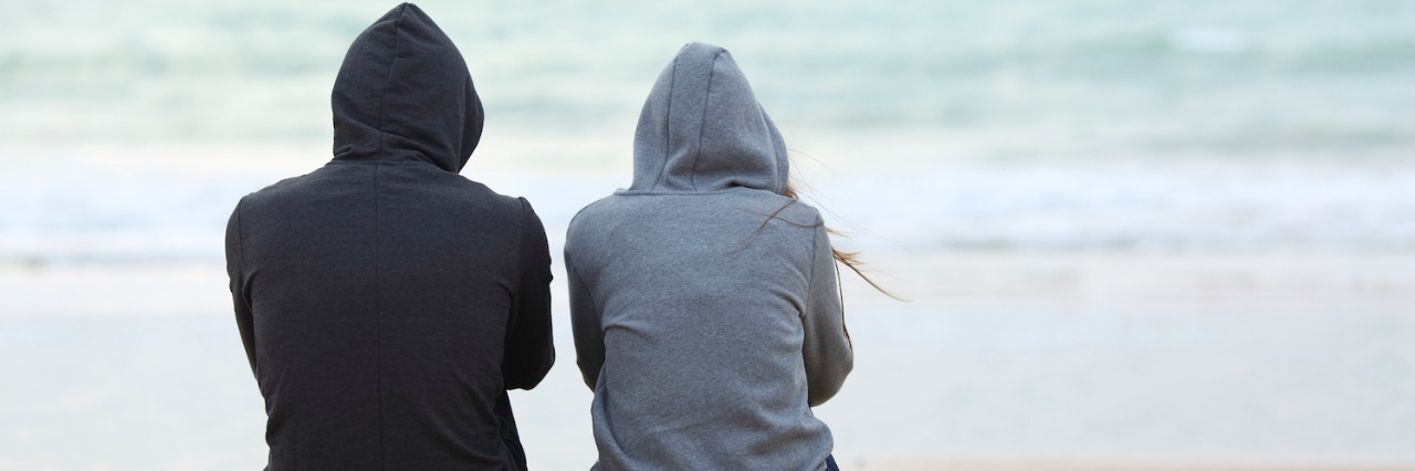 Two people wearing hoodies, sitting on sand on beach facing ocean