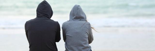 Two people wearing hoodies, sitting on sand on beach facing ocean
