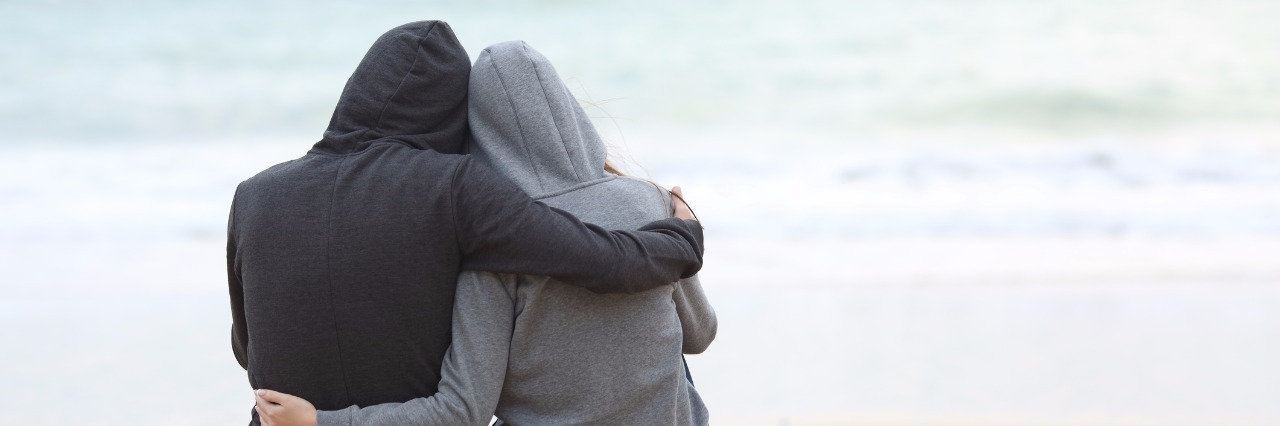 two people wearing sweatshirts and hugging on the beach