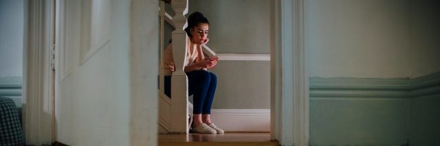 Teenage girl sitting at the bottom of a staircase using a smartphone.