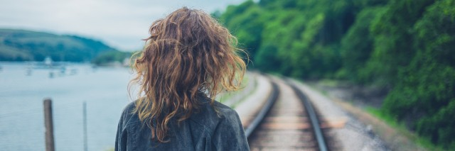 A young woman walking on the railroad tracks