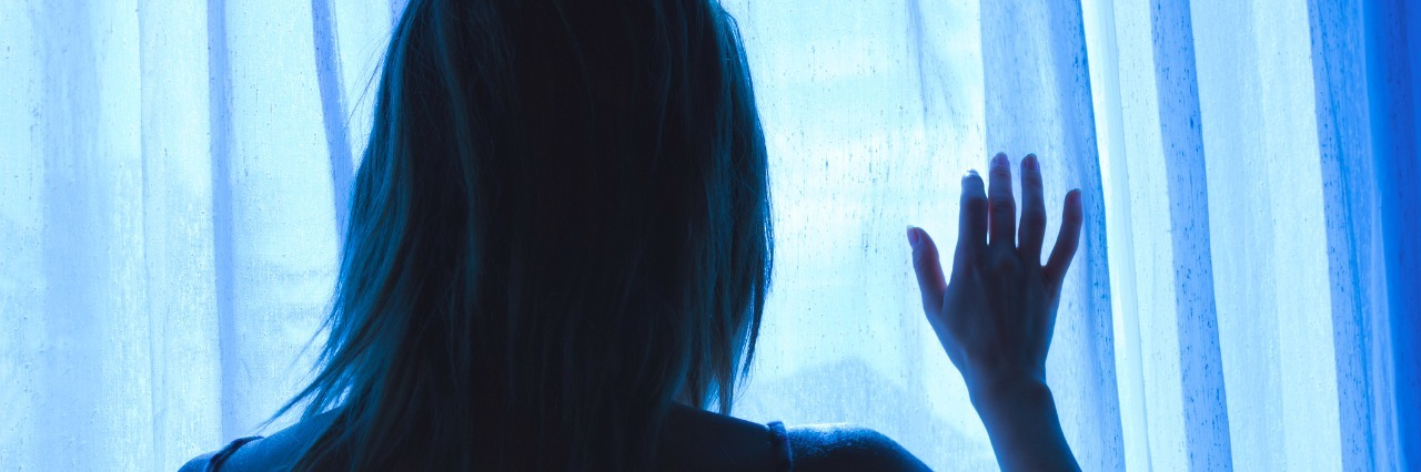 Lonesome girl holding a curtain at night looking out window