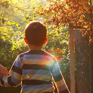 Boy wearing striped shirt, walking in park holding mom's hand on sunny day