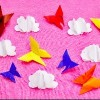 Pink background with paper multicolored butterflies and clouds. toning. selective focus