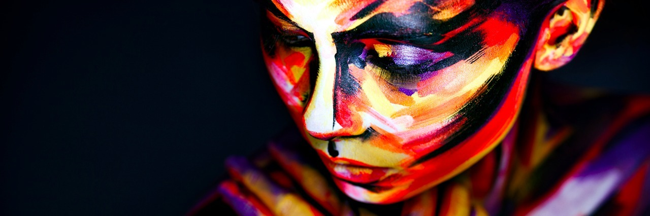 woman's face and arms covered in multicolored paint