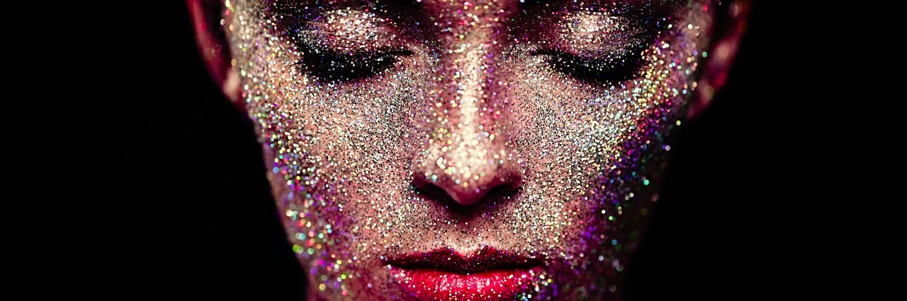 Portrait of woman with sparkles on her face. Girl with art make up in color light. Fashion model with colorful make-up