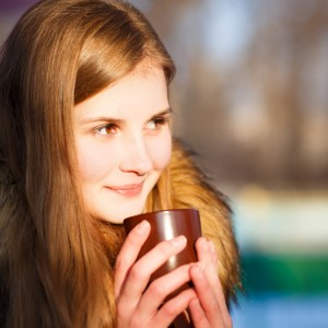 Young girl holding cup of coffee in winter park