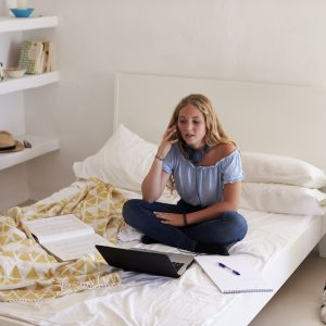 Teenage girl on phone doing homework on her bed with laptop