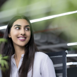 Portrait of young Latin-American businesswoman sitting at computer in office, looking away and smiling