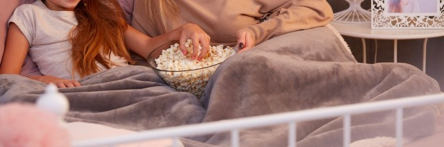 Mother and daughter watching film in bed, eating popcorn