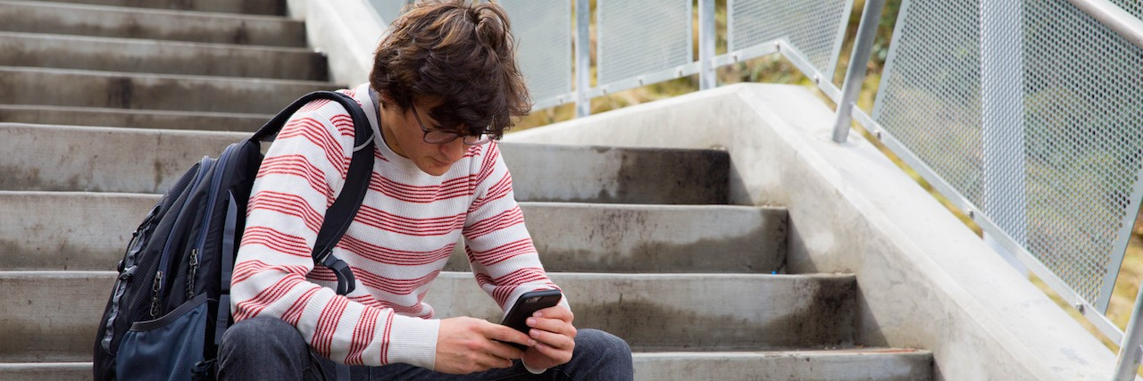 teen sitting on steps, looking at this phone