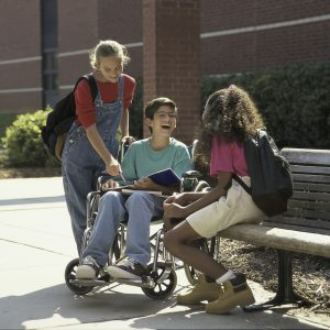 Boy in a wheelchair talking to two girls outdoors