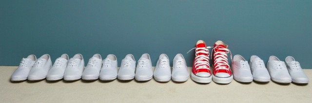 Pair of shoes in row against wall, all white and one red