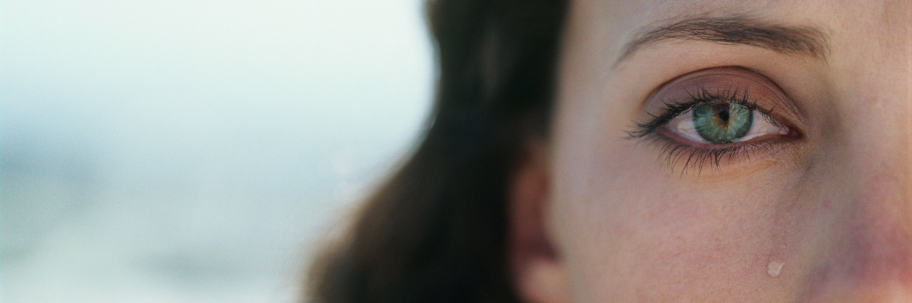 Young woman crying,portrait,close-up (cropped)