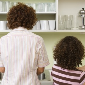 Mother and daughter in front of sink in kitchen